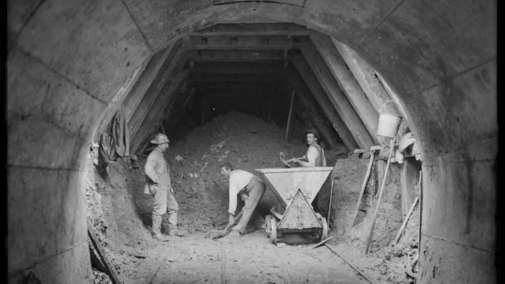 b&w photo of 3 men digging a tunnel, 1902